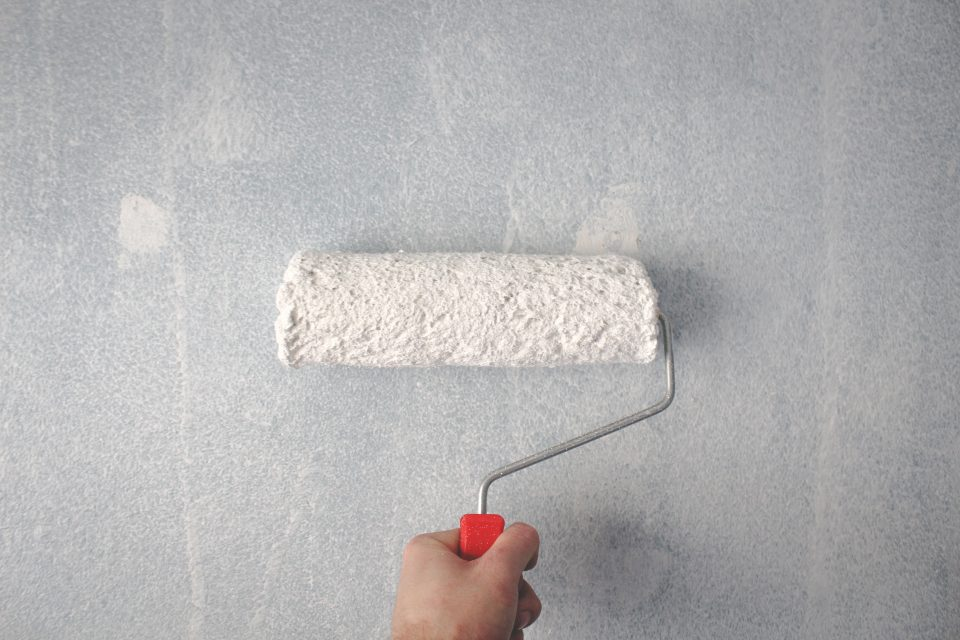 Person holding paint roller on wall