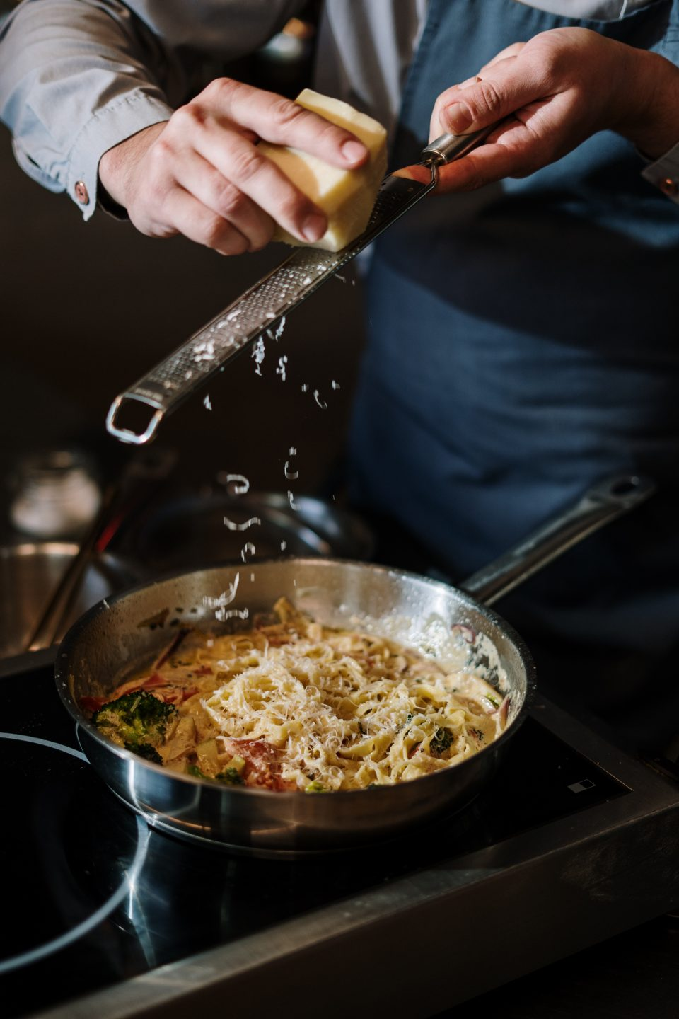 Person holding stainless steel cooking pot with pasta
