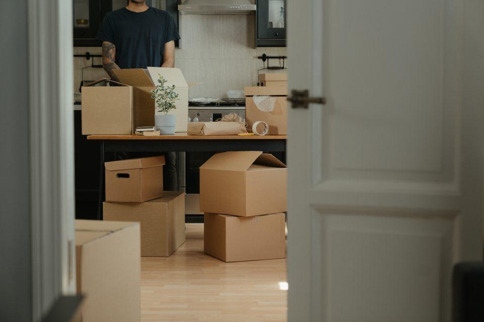Man in black shirt standing near brown cardboard boxes