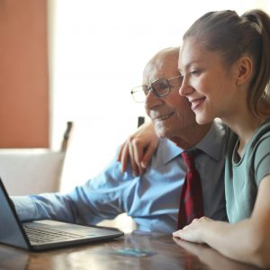 Young positive woman helping senior man using laptop