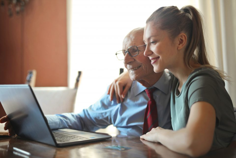 Young positive woman helping senior man using laptop
