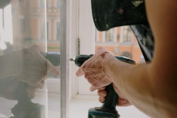 Crop man screwing metal detail on window
